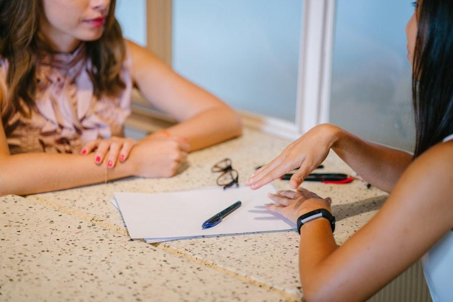 two women sitting down with their elbows on the table, along with a paper, two pens, and glasses.