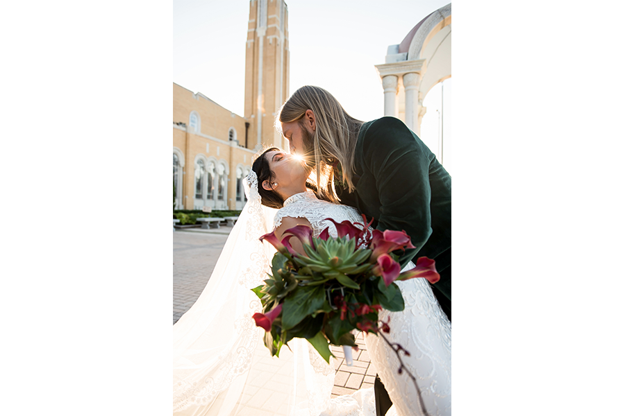 A wedding photography image of the bride and groom as the groom dips the bride and there is a sunburst between their lips.