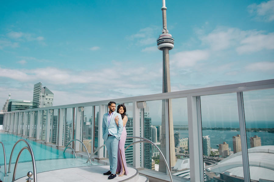 An engagement session on the rooftop of a building with a pool and the skyline behind them.