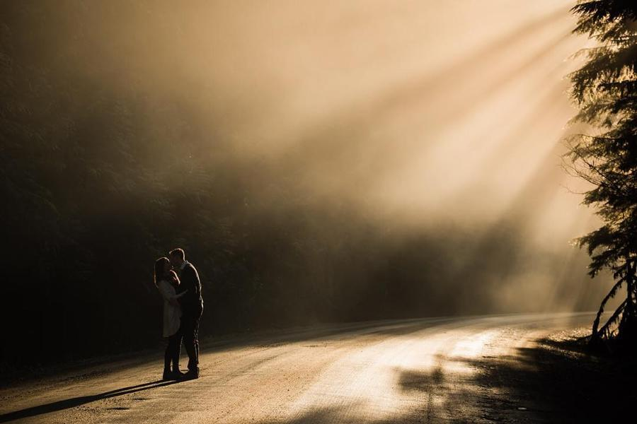 A couple standing on a sunlit pathway that is surrounded by trees