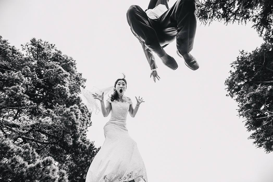 Bride and groom striking a pose mid air  creating a unique wedding photo