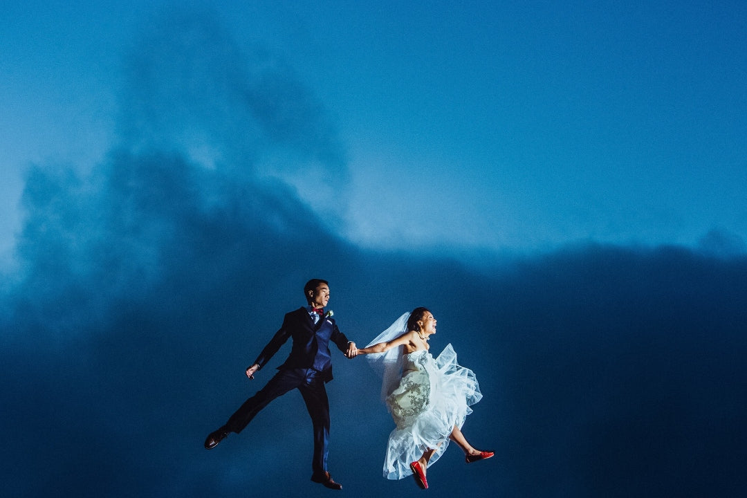 Bride and groom doing a jump shot while holding each other's hand