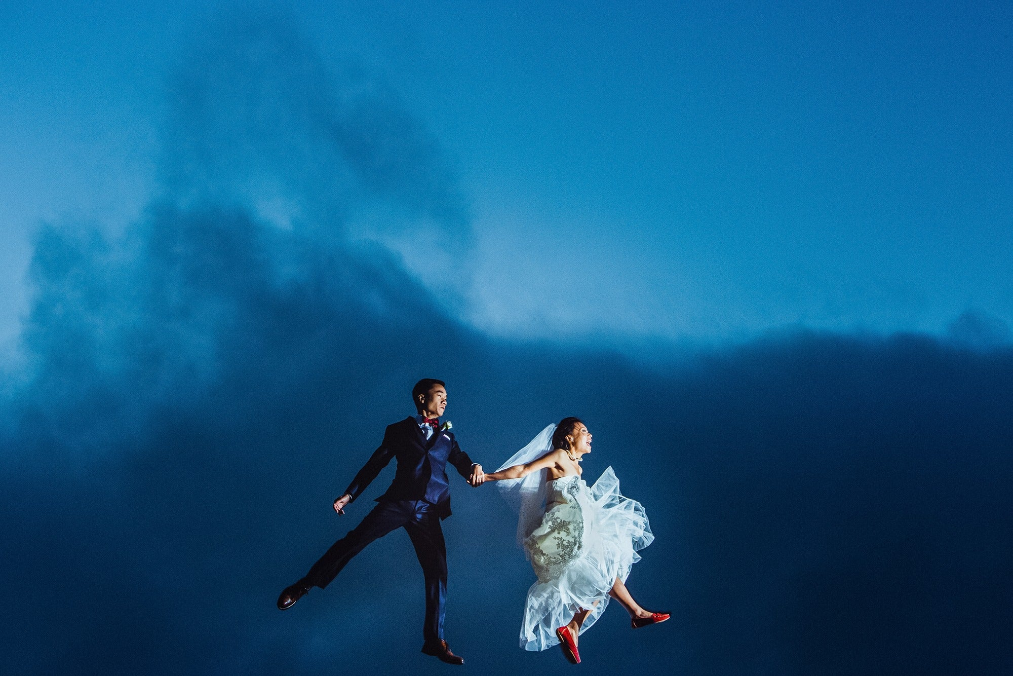 Bride and groom holding hands during a jump shot against a blue sky