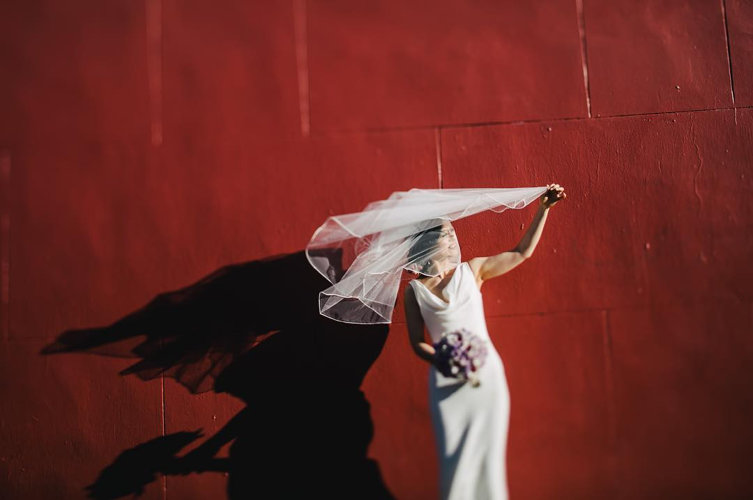 A bride posing for a picture in front of a red wall while holding the veil over her face
