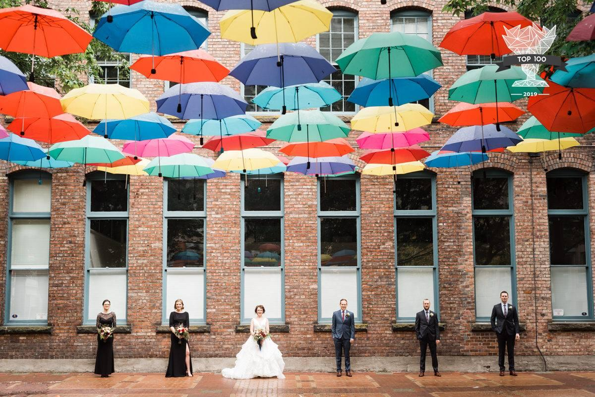 bridal party photos with party standing under color umbrellas