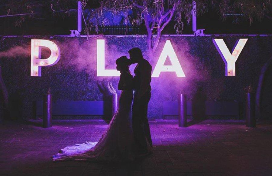 Silhouette of a couple posing in front of LED Letter Lights displaying - PLAY