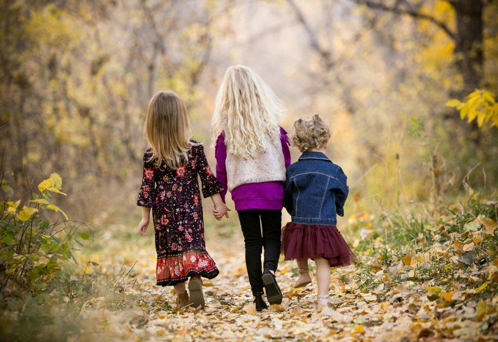 Three young girls walking hand-in-hand through the woods