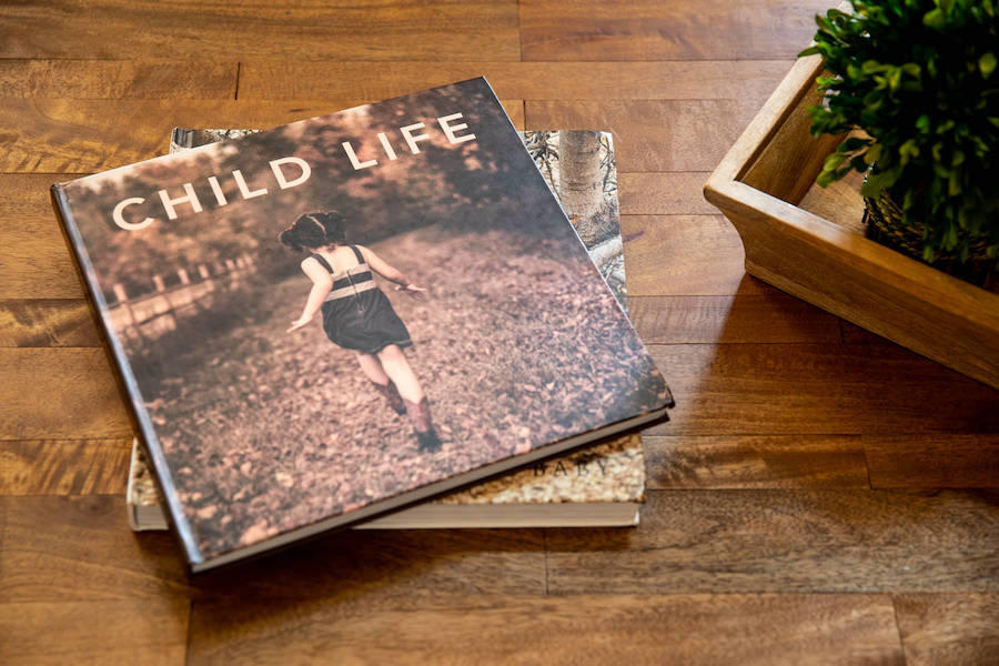 Children's photography book named Child Life placed on top of a wooden table