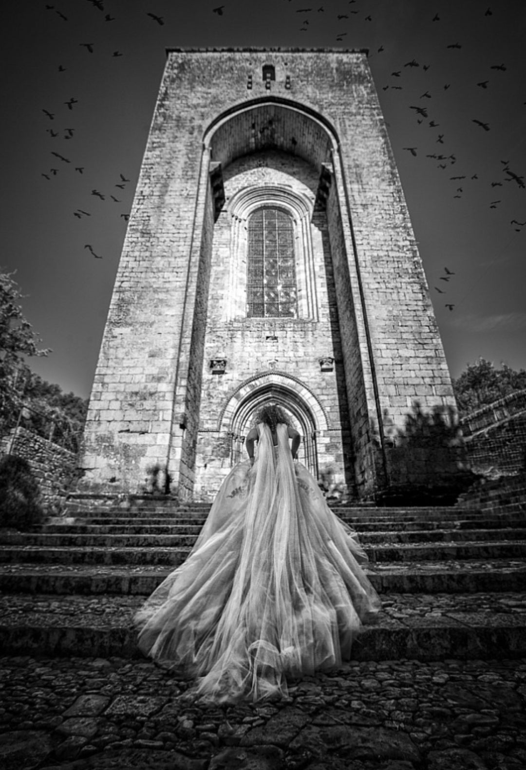 Black and white photograph of a bride climbing the stairs with the veil and the train of her dress following