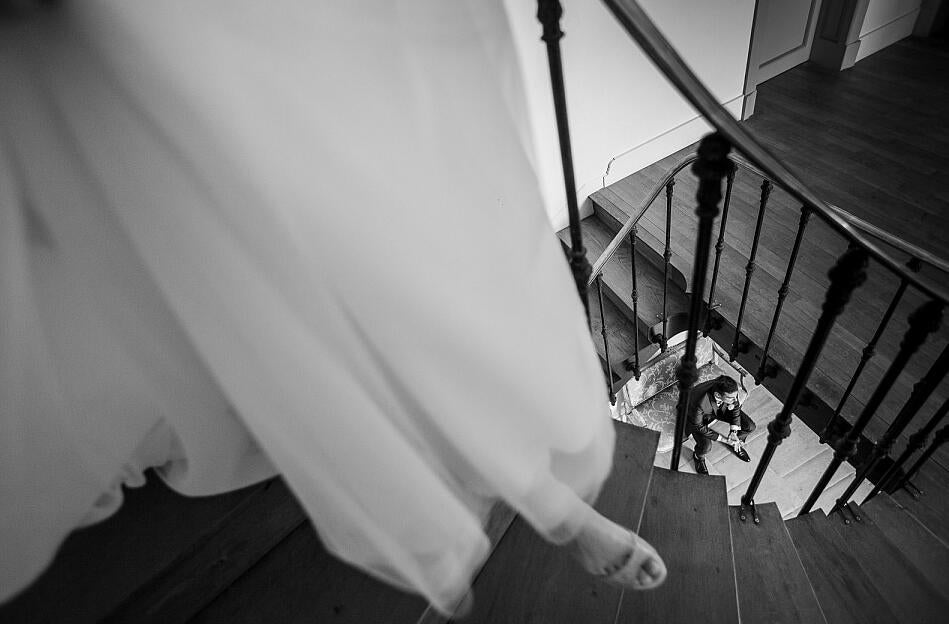 black and white image of a bride walking down stairs to groom