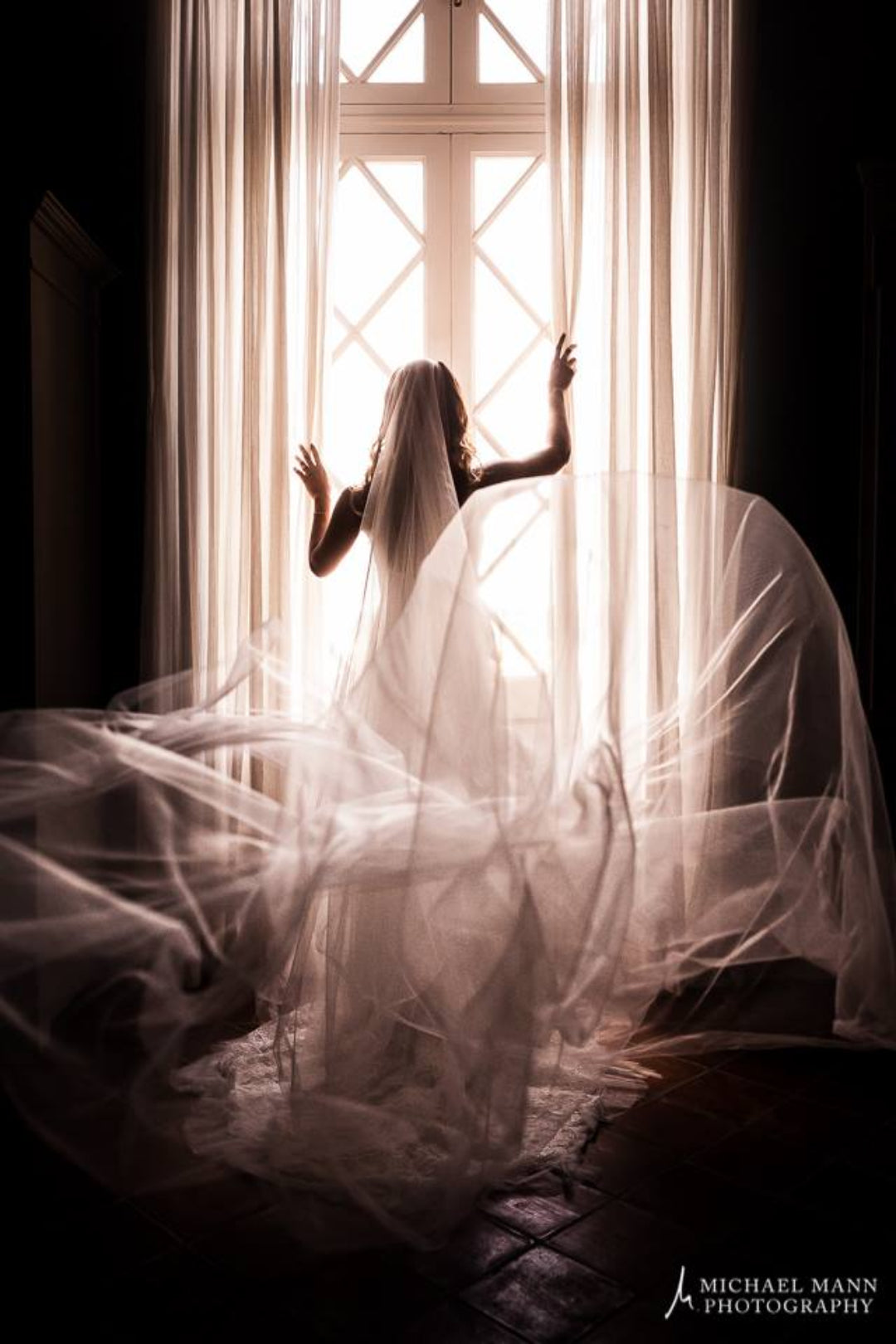 Dramatic back shot of the veil and train of the dress as the bride looks the other side through the window
