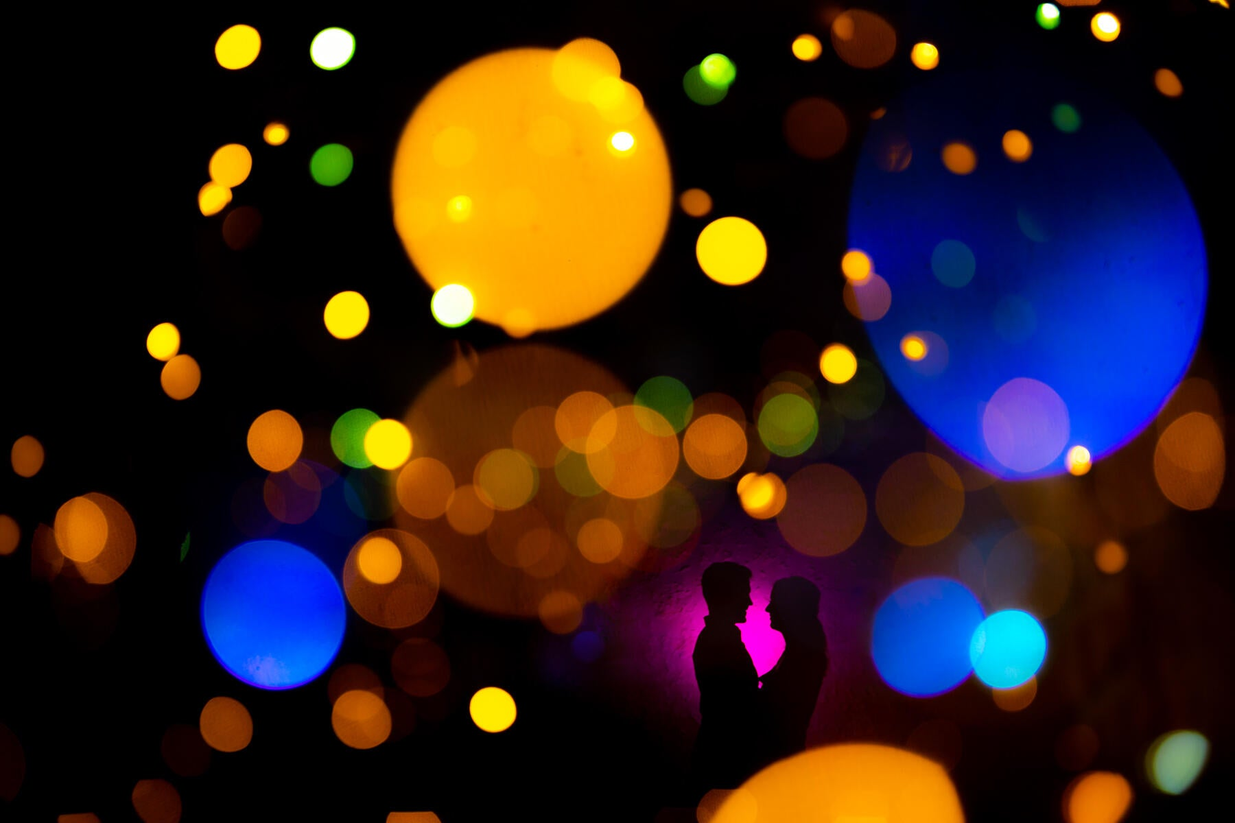 brightly colored lights in the image with silhouette of two people facing each other
