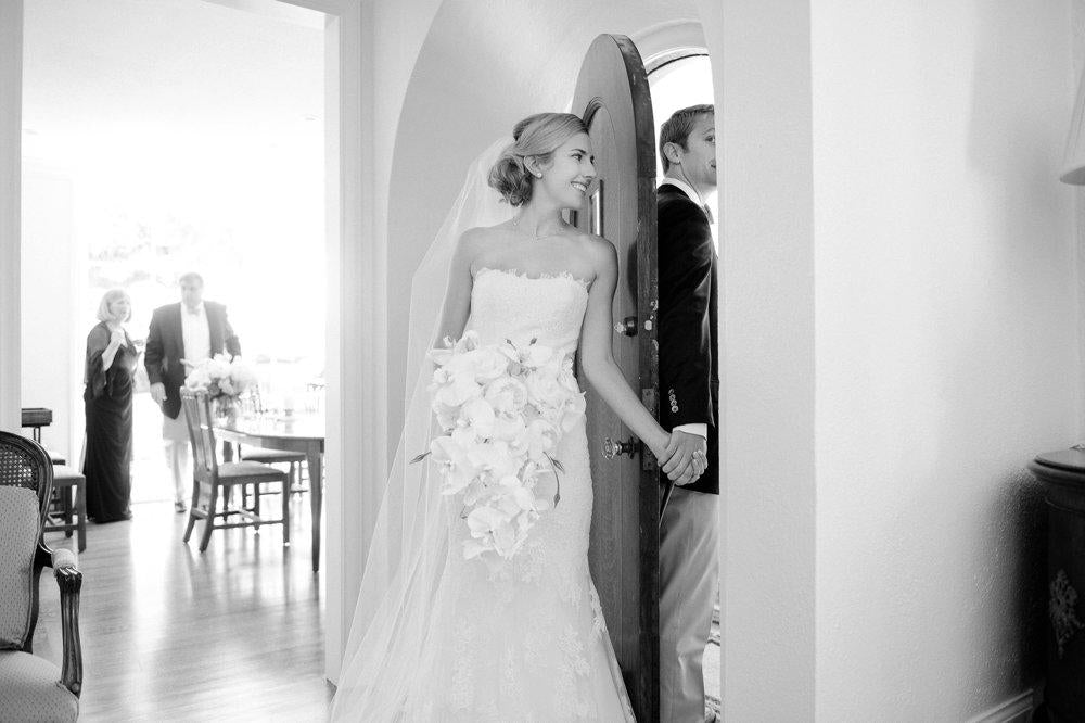 A black and white image of a bride and groom holding hands
