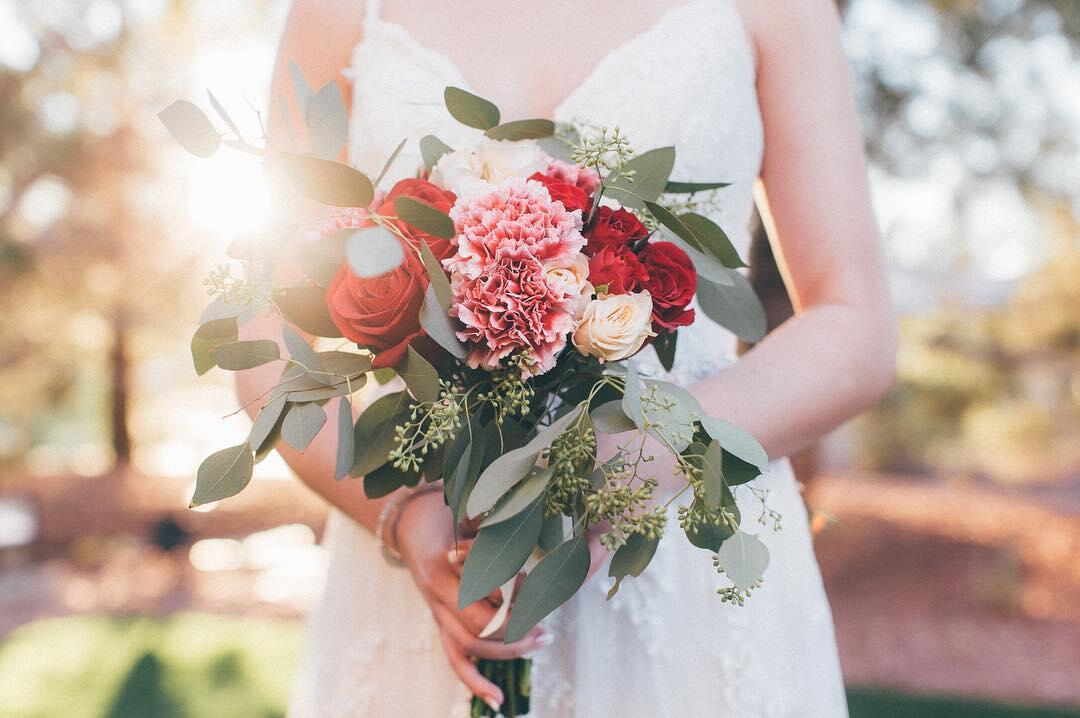 Close up shot of a bride's hand holding a bouquet with red, pink, and white flowers.