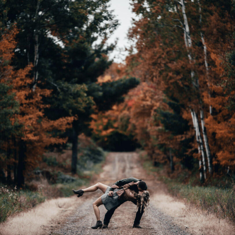 couple dipping on a road in a fall forest