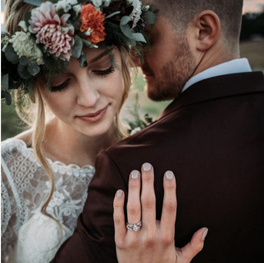 Mid-close up shot of a couple hugging each other with the bride's hand on the groom's back highlighting the wedding ring