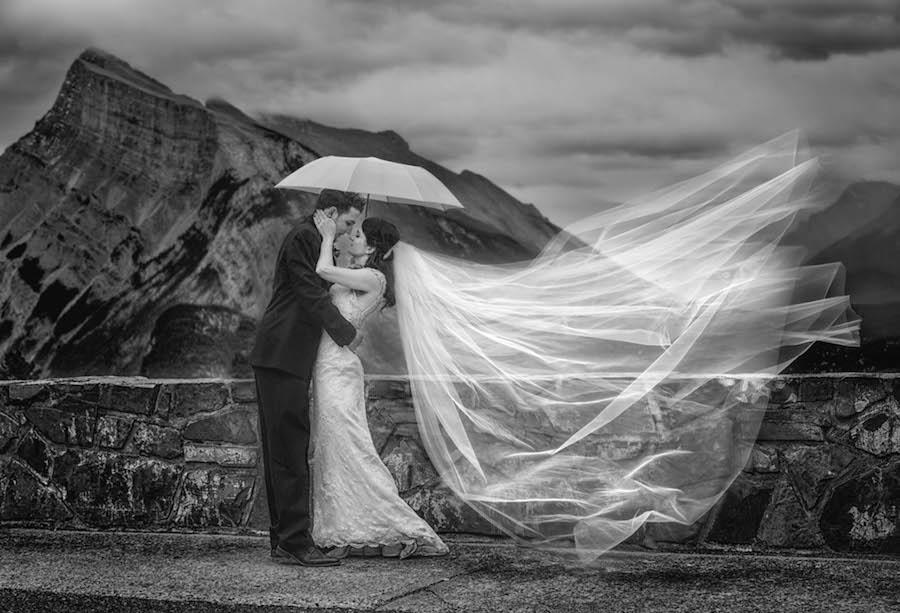 couple under and umbrella with the bride's veil in the air
