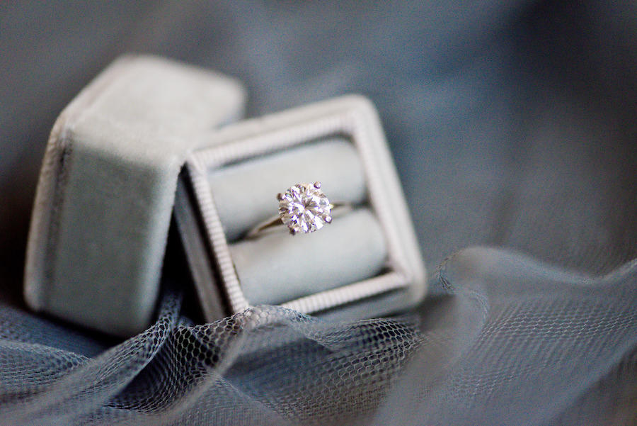 Silver wedding ring in a silver box with net underneath the box.