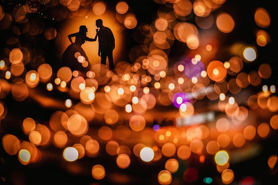 Silhouette image of a bride and groom with a bokeh background - Stellar example of how to shoot a wedding by Robb McCormick