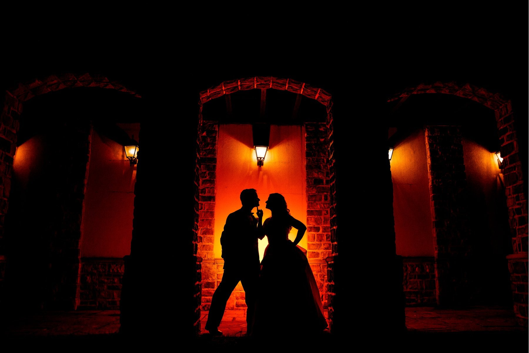 Silhouette of a couple posing in front of a red light source