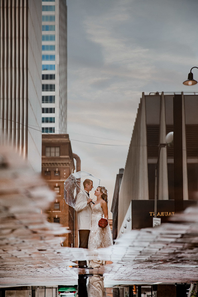 Gorgeous capture of a bride and groom posing under an umbrella through a reflection on the water on the floor