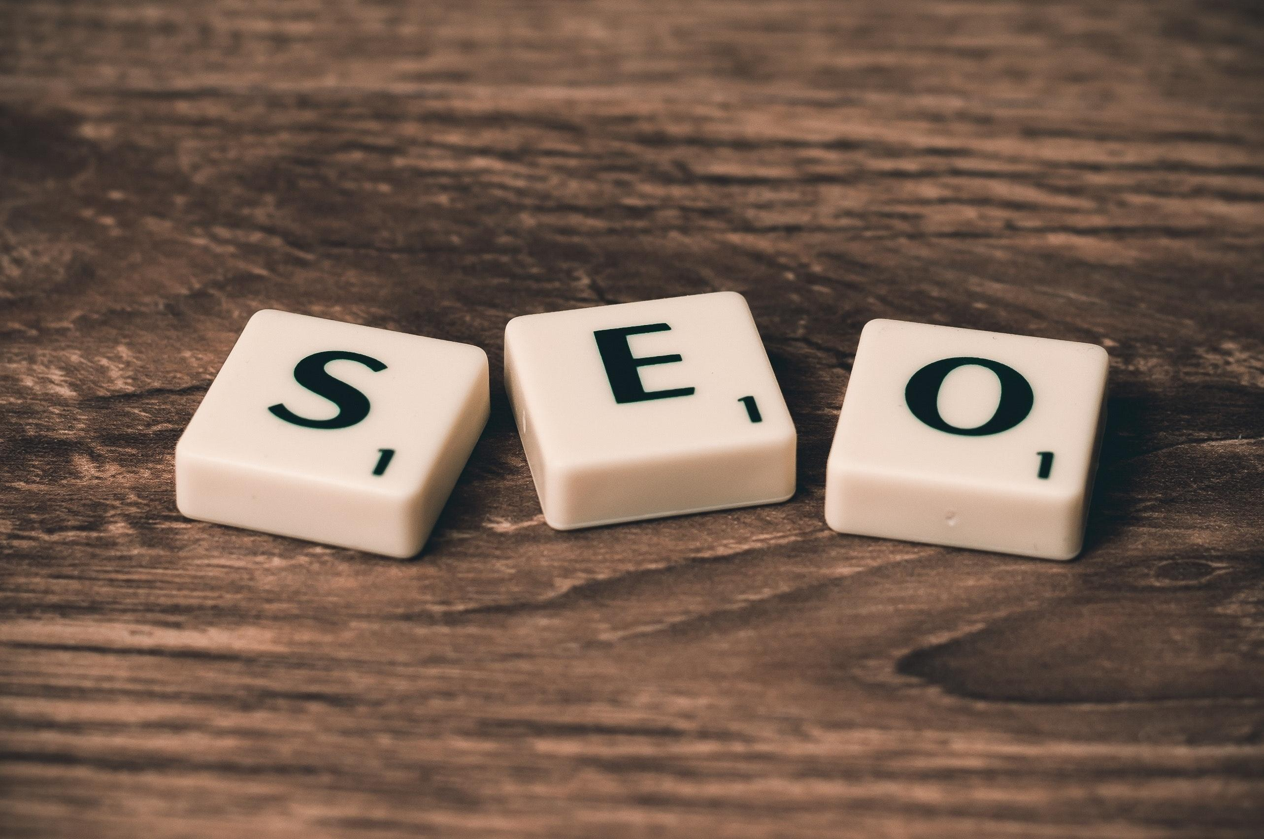 3 1-point Scrabble pieces that spell out SEO on a brown surface - SEO for photographers