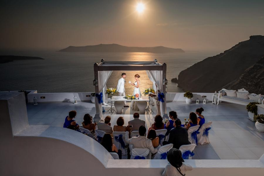A couple reading vows in front of a seaside setting during sunset