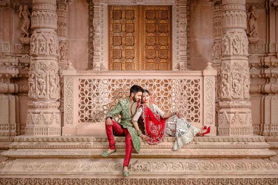 A couple dressed in Indian clothing posing in front of a structure with intricate architectural design