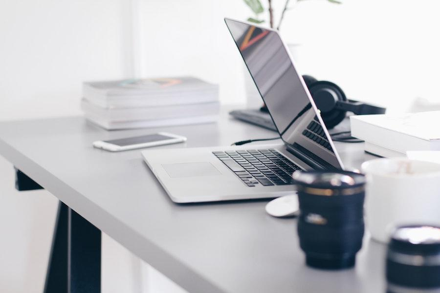 A laptop computer on a gray desk with books, a cell phone, and two lenses surrounding it.