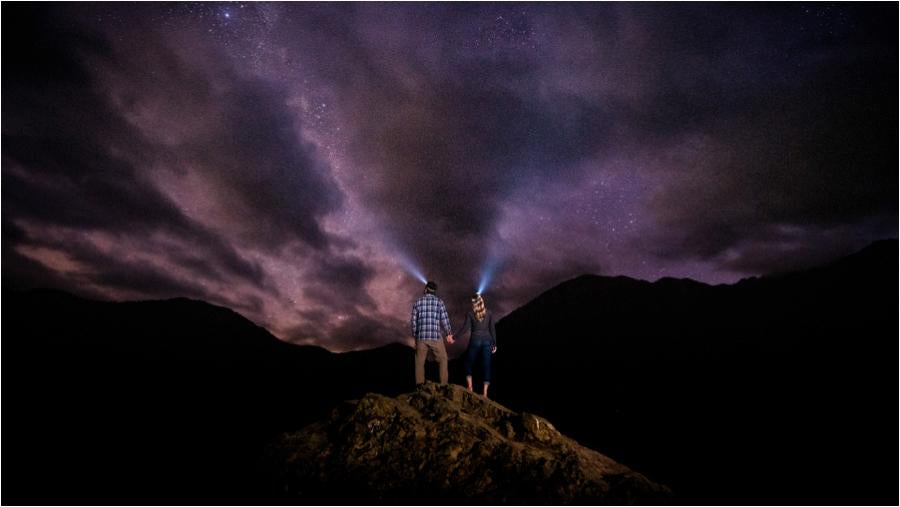 dark and starry night photo showing stars, clouds and a couple holding hands wearing headlamps