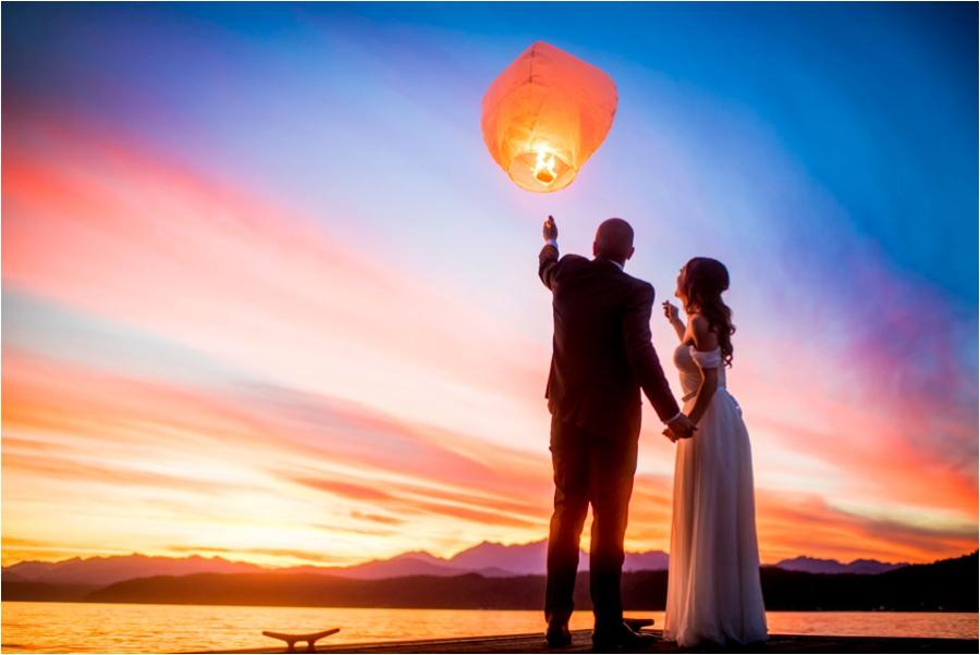 couple letting a lit lantern float off into the sky near a lake at sunset