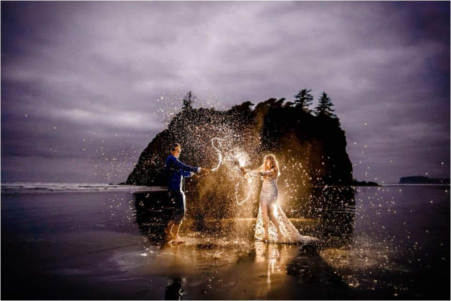 couple popping a champagne bottle and spewing champagne everywhere near a rock in the ocean wearing a wedding dress and tux