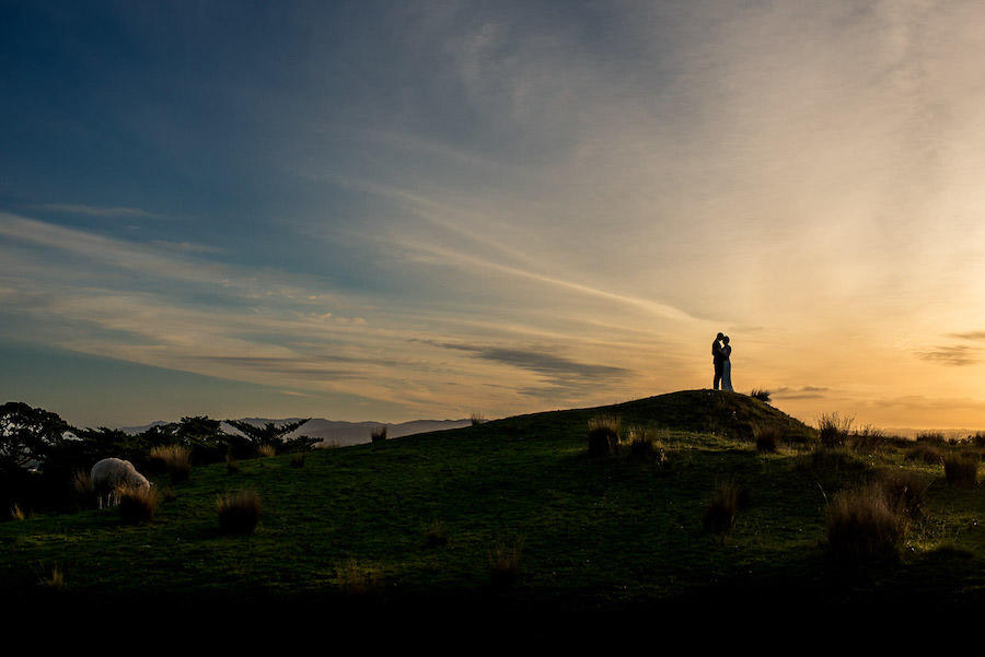 A wedding photo of the couple standing on a hill with the sunset out of the photo, causing a silhouette of them.