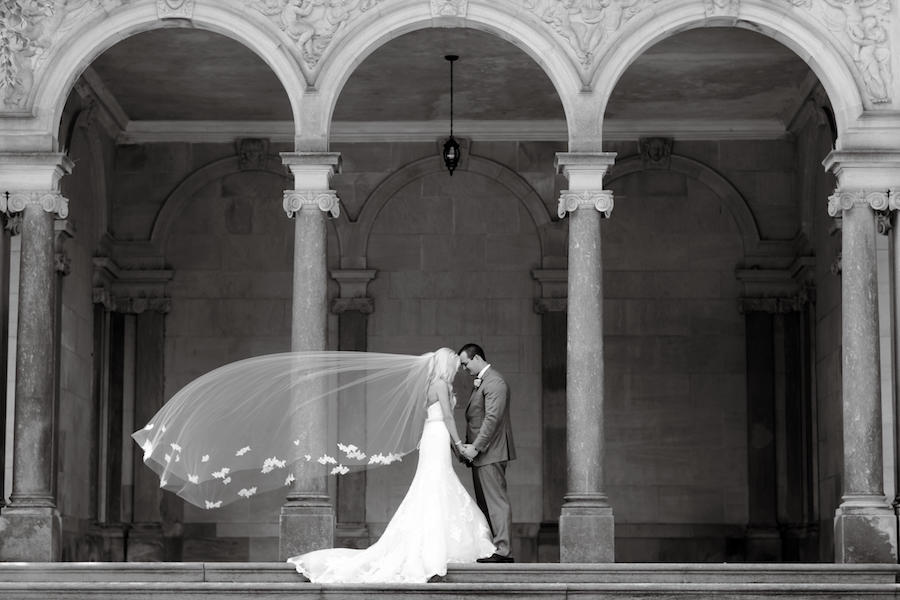 A black and white photo of a bride & groom outdoors, with the bride's veil flowing in the wind.