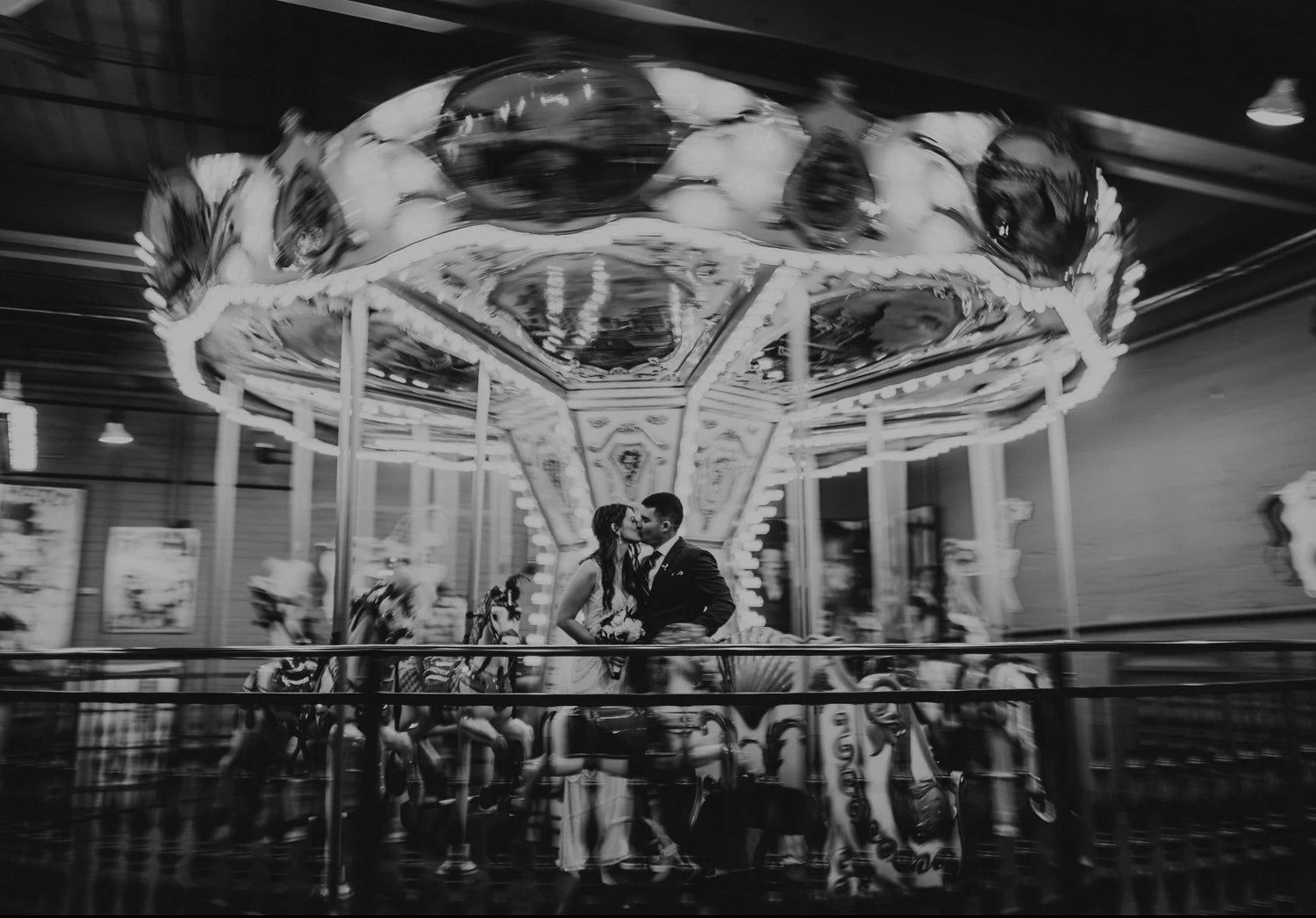 Black and white unique wedding photo of the carnival carousel in motion as the couple pose in front of them
