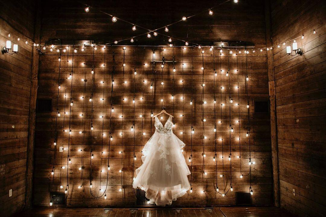 A wedding gown at display in front of a backdrop decorated with fairy lights