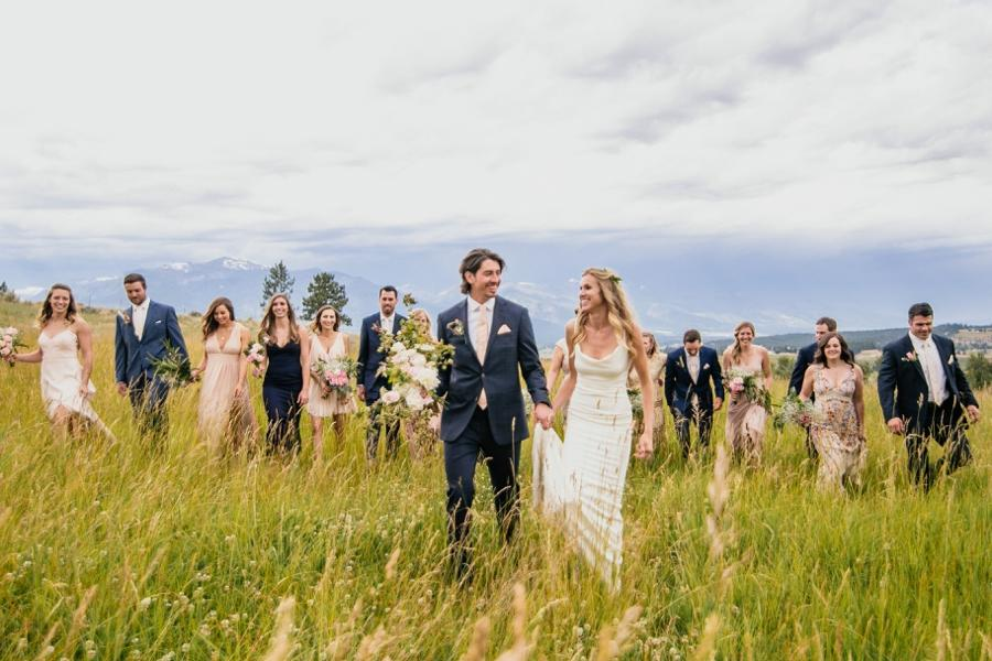 Bridesmaids and groomsmen walking alongside the bride and groom on a farm