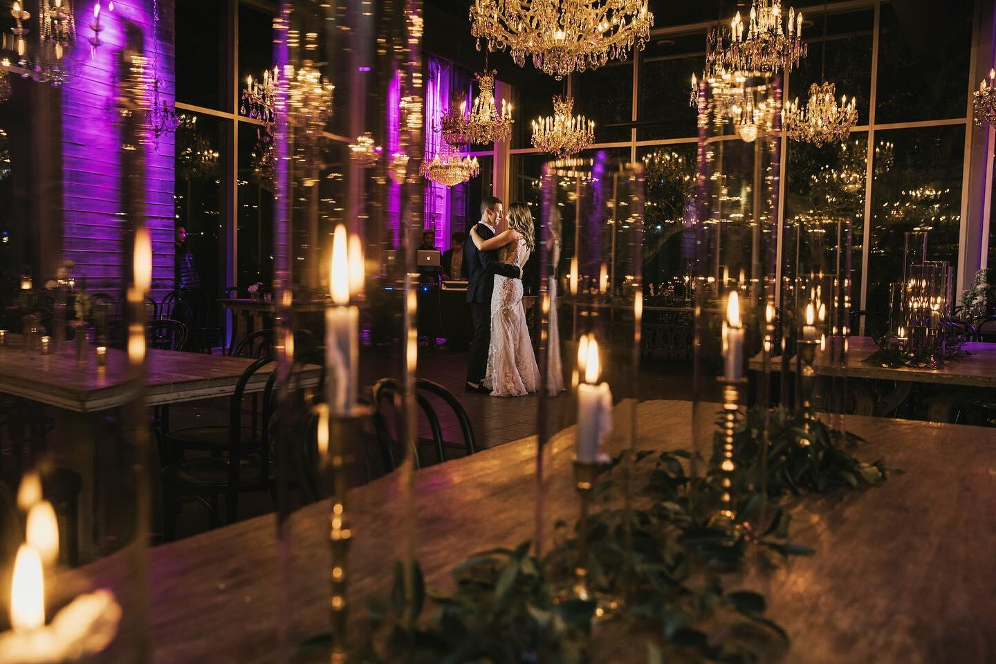 A glimpse of the bride & groom dancing in a hall decorated with chandeliers & candles