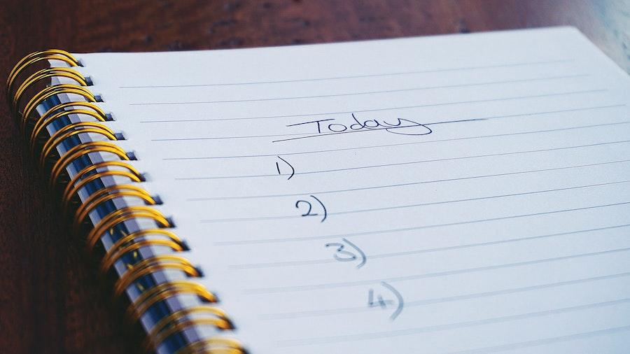 """A notebook on a brown flat surface with the word """"Today"""" & 1 to 4 numbered to-do list for the photography workflow."""