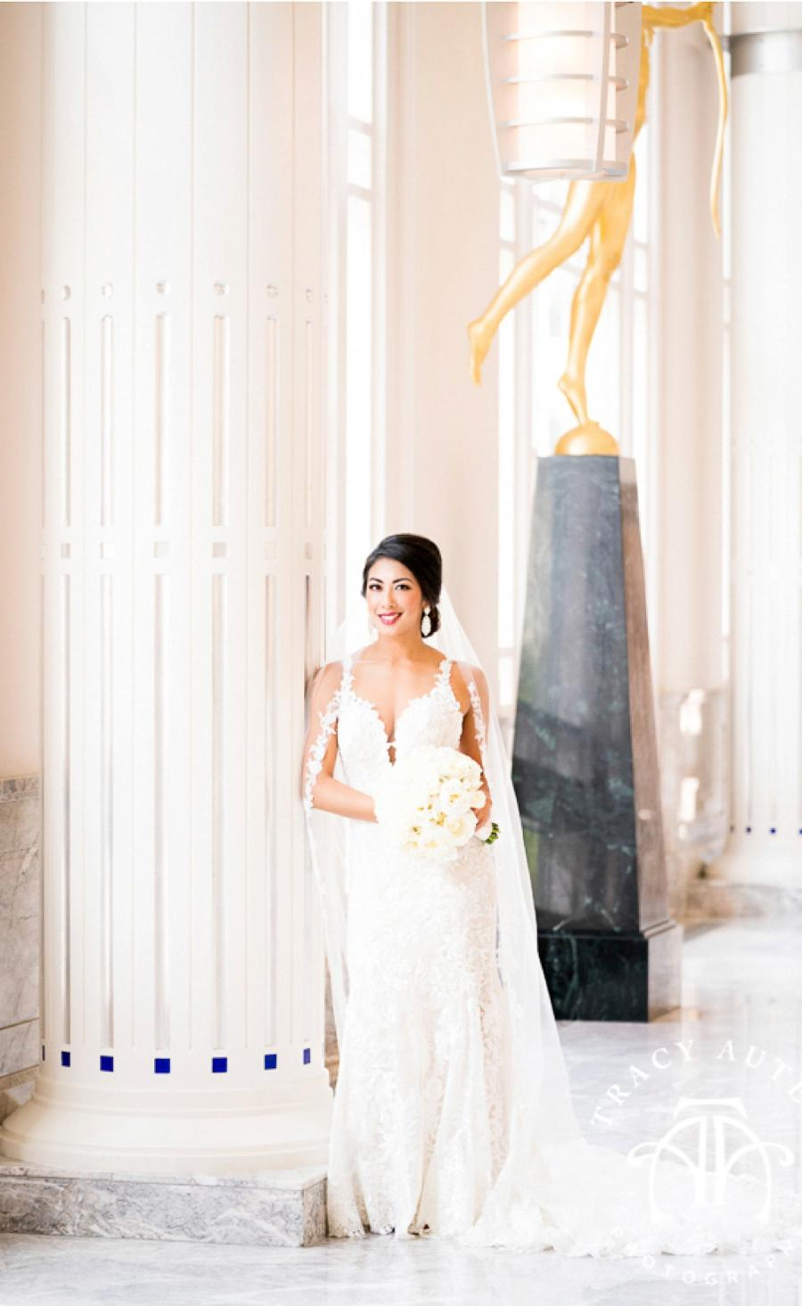 A bride posing against a pillar with a bouquet of flowers in hand