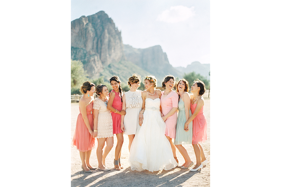 bridal party standing outside with a mountain in the background