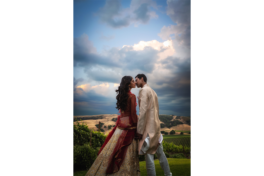 A wedding photo of the couple standing on top of a hill with the a blue sky behind them.