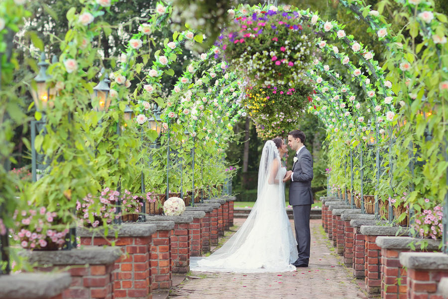 A wedding image of the couple standing face to face under an arch of flowers.