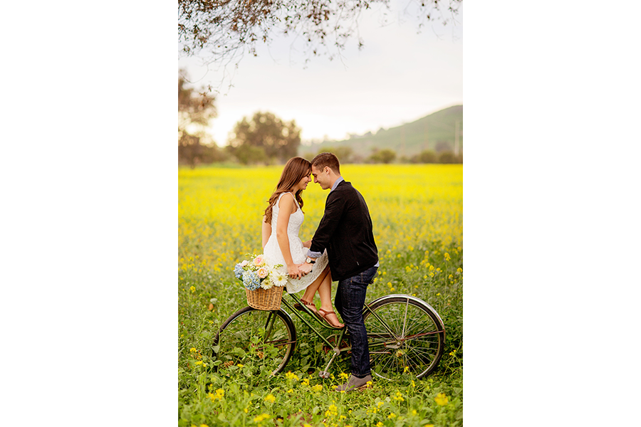 A couple sitting on a bike with a flower basket attached in a green grass field.