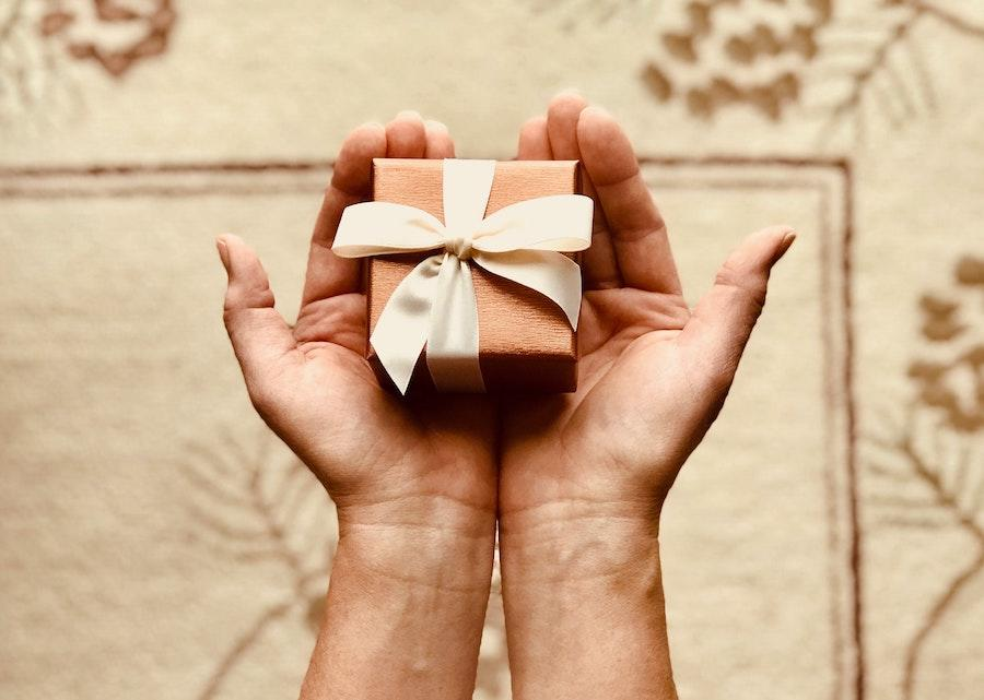 person holding small gift box in their hands