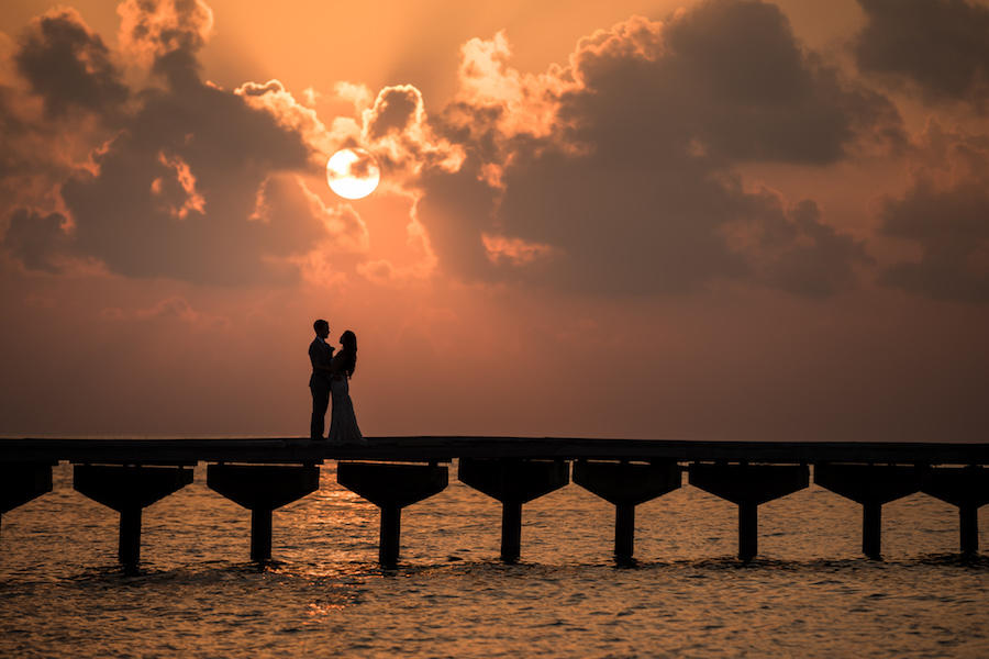 A wedding silhouette image of the couple standing on a pier over the water, with the sun setting in the clouds behind them.