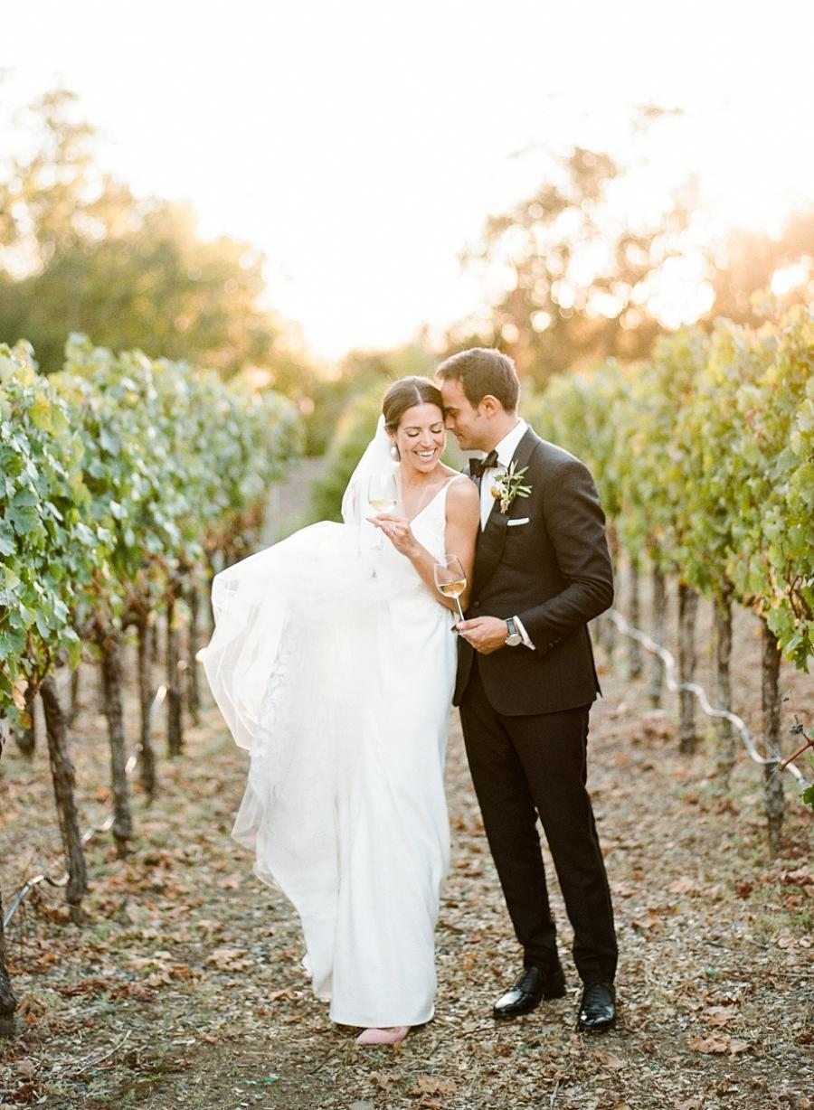 A bride and groom posing with wine in hand at a vineyard
