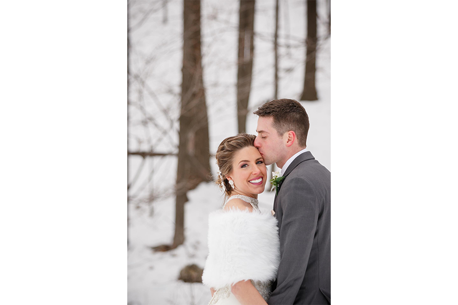 An outdoor wedding photography couple portrait of the bride and groom, with the groom kissing the side of bride's forehead as she faces the camera and smiles.