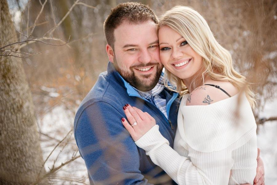 An outdoor winter engagement session image of the couple in an embrace facing toward the camera, with the bride's hand on the groom's chest and her ring showing.