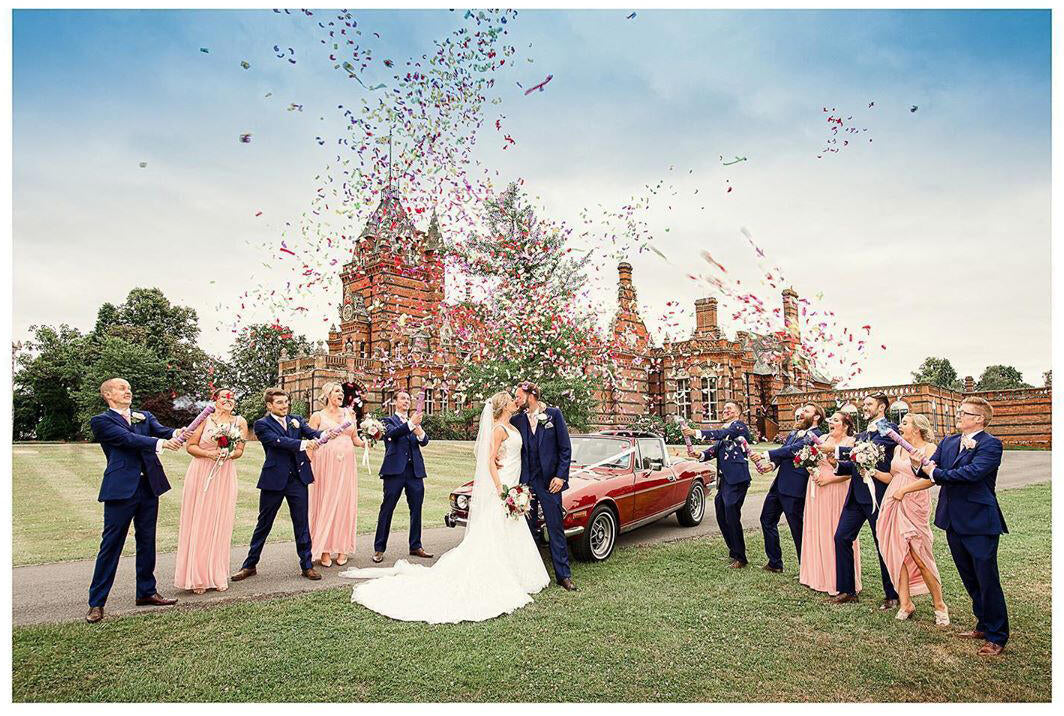 bridal party photos with bridal party throwing confetti and a classic car near a castle